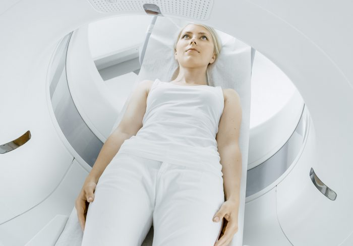 Close-up Portrait of a Female Patient Lying on a CT or MRI Scan,